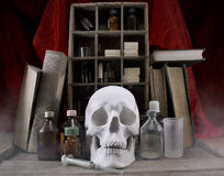 Old pharmacy alchemist table. Old pharmacy medicine alchemy table with bottles on shelves, books, skull and dirty syringe royalty free stock photo