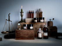 Old pharmacy. bottles, jars, scales, candle on wooden shelves Royalty Free Stock Images