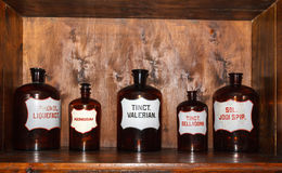 Old pharmacy cabinet. With drugs in glass bottles with labels royalty free stock photography