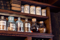Old pharmacy remedies in glass jars. For making balm located on shelfs with old books stock photography