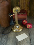 Old phone and a blank note. An old golden colored phone on a rustic table with a blank note Stock Photography