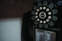Old phone in phone booth closeup. Close up of old payphone in phone booth of bar royalty free stock photo