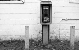 Old phone booth station. Phone booth station outside a concrete block building Royalty Free Stock Images