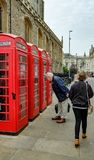Senior male seen looking into an old fashioned, British phone box in Cambridge, UK. royalty free stock images