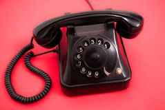 Old phone with dials on red background. Old black rotary phone with dials ring  on red background. Close up Stock Photography