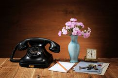 An old phone, flowers in a vase and an alarm clock royalty free stock photo