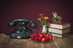 Old Phone and fresh cherries Stock Photography