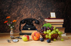 Old phone, fruit and books Stock Image
