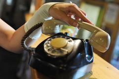 Old phone. Hand holding the handset and an old phone Royalty Free Stock Photo
