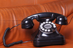 Old phone on leather sofa Royalty Free Stock Images