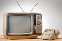 Old phone and old tv vintage style. On gray background Royalty Free Stock Image