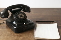Old phone with pad and pencil. Old phone with writing pad for Copy Space and pencil on a desk Royalty Free Stock Photos