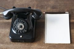 Old phone with pad and pencil Stock Images