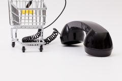 Old phone reciever and cord connection with shopping trolley. Stock Images