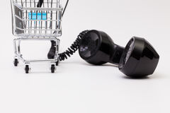 Old phone reciever and cord connection with shopping trolley. Stock Photos
