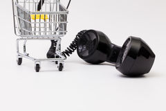 Old phone reciever and cord connection with shopping trolley. Royalty Free Stock Photo