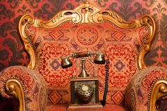 Old phone is a red chair with gold accents. Red vintage wallpaper. Focus on phone Stock Photography