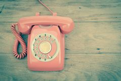 Old phone rotary vintage retro stlye telephone on wood table top. View royalty free stock photo