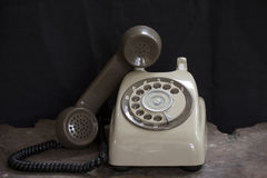 Old phone on a table , rotary disc on wooden table grunge background.  Stock Images