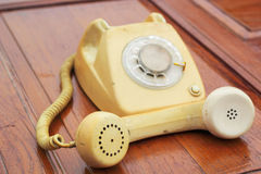 Old phone vintage style on the wooden floor. Royalty Free Stock Images