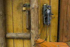 Old phone on a wooden lodge. Old phone on yellow boards and doors Royalty Free Stock Photography