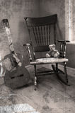 Old Photo. A rocking chair with a teddy sitting on it and a guitar beside it Royalty Free Stock Image