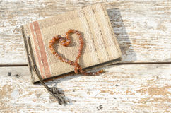 Old photo album with amber necklace heart Royalty Free Stock Images