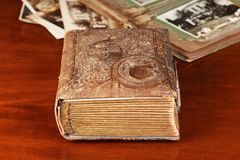 Old photo album and pictures. On wooden table Stock Photos