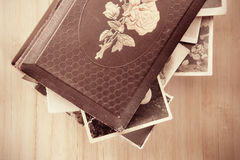 Old photo-album. Old photo-album with retro pictures inside it on wooden background stock photo