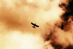 Old photo Antonov An-2 - multipurpose aircraft in the clouds. Airplane in the Clouds - effect of old photo stock images