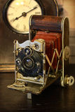 Old Photo Camera And Clock. Old photo camera with bellows and clock on wooden table Royalty Free Stock Photos