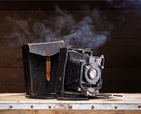 An old photo camera on a dark background Stock Photography
