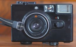 Old photo camera. Isolated on a wooden background. 35 mm color film was use in this camera Royalty Free Stock Photos