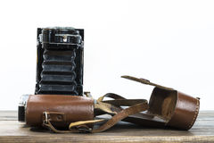 Old photo camera. In leather case on a wooden desk Royalty Free Stock Images