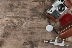 Old photo camera, lens cap, tripod and brown carrying case on wooden background. Royalty Free Stock Image