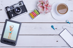 Old photo camera, tablet, smartphone, headset on a wooden table. With copy space. A cup of hot coffee and biscuits on a wooden table Royalty Free Stock Photo