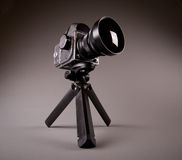 Old photo camera with tripod on grey in Hi-Res Royalty Free Stock Images