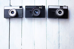 Old photo camera on a white wooden background. Old camera on white wooden background Royalty Free Stock Photo