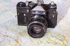 Old photo camera on world map Stock Photos