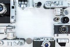 Old photo cameras, film rolls, lens and tripod on white wooden b. Ackground. frame design. flat view Stock Photography