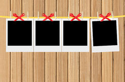 Old photo cards hung with wooden hangers over wooden wall Royalty Free Stock Photo