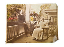 Old Photo of Couple on a Porch. A vintage photograph of an older couple sitting on the porch of their home.  It's sepia with some parts colorized Royalty Free Stock Photo