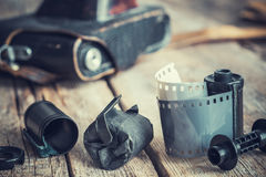 Old photo film rolls and cassette, vintage camera on background. Stock Photos