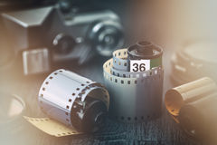 Old photo film rolls and retro camera on background. Stock Photo