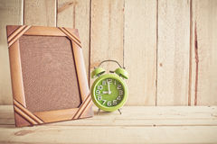 Old photo frame and clock on wooden table over wood background Royalty Free Stock Photo