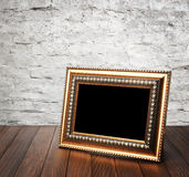 Old photo frame on the wooden table Stock Photography