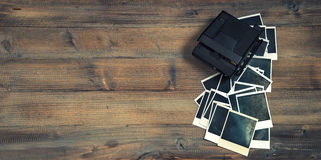 Old photo frames and camera on rustic wooden background. Retro style toned picture Stock Image
