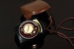 Old photo light meter in a case on a mirror table royalty free stock image