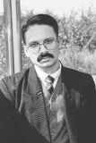 Old photo of man in suit with a mustache and glasses on the trai Stock Images