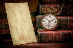 Old photo paper texture, pocket watch and books. Vintage wood desk with old photo paper texture, books and old pocket clock in low-key. Concept of time,the past Royalty Free Stock Image